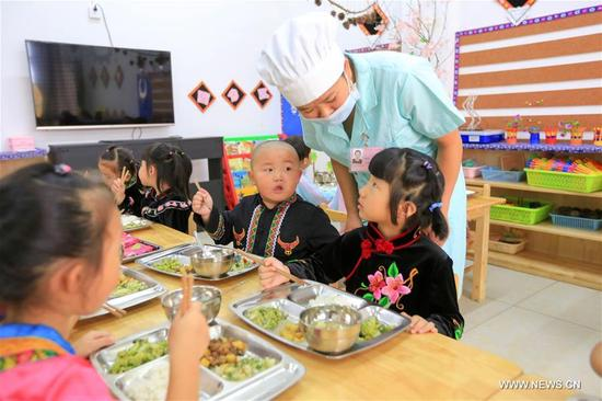 Children take free lunch at the Kaihuai Community No. 13 Kindergarten, which was newly built for children relocated from poverty-stricken areas, in Kaili City, Miao and Dong Autonomous Prefecture of Qiandongnan, southwest China's Guizhou Province, Sept. 6, 2017. Nutrition program has benefited preschool children in rural area of Kaili since spring this year, with free breakfast and lunch offered to children at rural kindergartens and kindergartens for children relocated from poverty-stricken areas. (Xinhua/Wu Jibin)