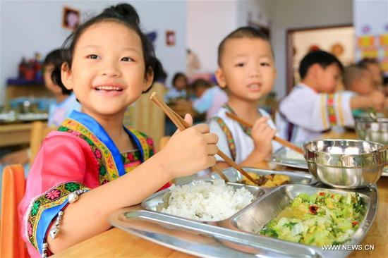 Yang Fengqin (L), a 4-year-old girl of Miao ethnic group, takes free lunch at the Kaihuai Community No. 13 Kindergarten, which was newly built for children relocated from poverty-stricken areas, in Kaili City, Miao and Dong Autonomous Prefecture of Qiandongnan, southwest China's Guizhou Province, Sept. 6, 2017. Nutrition program has benefited preschool children in rural area of Kaili since spring this year, with free breakfast and lunch offered to children at rural kindergartens and kindergartens for children relocated from poverty-stricken areas. (Xinhua/Wu Jibin)
