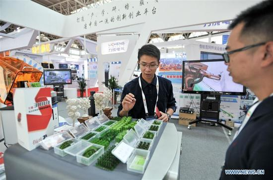 A staff member introduces the 3D printing technology to a visitor during a high technology and equipment show of the China-Arab States Expo in Yinchuan, capital of northwest China's Ningxia Hui Autonomous Region, Sept. 7, 2017. Nearly 200 pieces of exhibits from 126 exhibitors all across the country were displayed on the show. (Xinhua/Li Renzi)