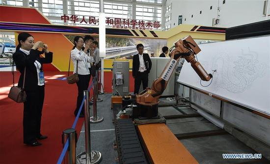 Visitors view an intelligent robot during a high technology and equipment show of the China-Arab States Expo in Yinchuan, capital of northwest China's Ningxia Hui Autonomous Region, Sept. 7, 2017. Nearly 200 pieces of exhibits from 126 exhibitors all across the country were displayed on the show. (Xinhua/Li Ran)