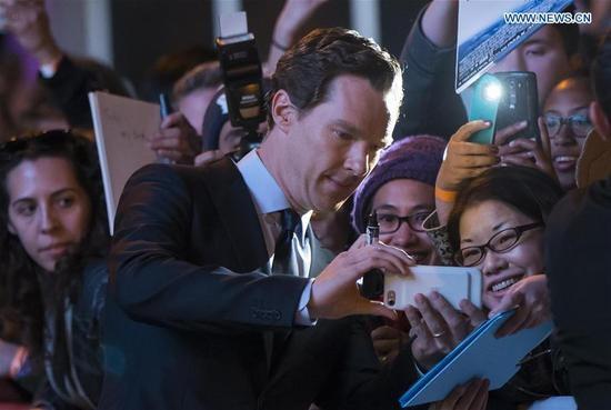 Actor Benedict Cumberbatch (C) poses for photos with fans as he attends the premiere of the film
