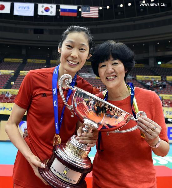 Lang Ping (R), head coach of Chinese Women National Volleyball Team, holds the trophy with her player Zhu Ting after the awarding ceremony for FIVB Women's Grand Champions Cup 2017 at Nippon Gaishi Hall in Nagoya, Japan on Sept. 10, 2017. Team China claimed the title with five victories in a row after round robin matches on Sunday. (Xinhua/Ma Ping)