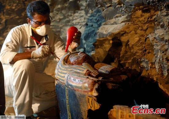 An Egyptian antiquities worker works on a coffin in the recently discovered tomb of Amenemhat, a goldsmith from the New Kingdom, at the Draa Abu-el Naga necropolis near the Nile city of Luxor, south of Cairo, Egypt, September 9, 2017.(Photo/Agencies)