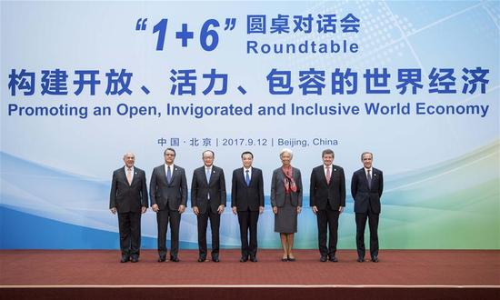 China's Premier Li Keqiang and heads of major international economic institutions pose for pictures before the