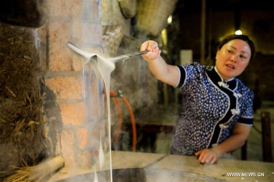 Li Hua makes snacks at a Chuanbeiliangfen restaurant in Nanchong, southwest China's Sichuan Province, Sept. 11, 2017. Li Hua, an inheritor of Chuanbeiliangfen, also called Clear Noodles in Chili Sauce, a provincial intangible cultural heritage in Sichuan, became attached with this special snack since she was 18 years old. Now Chuanbeiliangfen has become a famous brand. Thanks to Lanzhou-Chongqing railway, express highways and the Internet, Li has expanded her business to many provinces and cities in China. She hopes that her business would go abroad in the future. (Xinhua/Liu Chan)