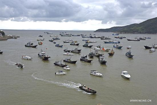 Fishing boats head towards a port in Jinqing Town of Taizhou, east China's Zhejiang Province, Sept. 12, 2017. China's National Meteorological Center (NMC) Tuesday issued a blue alert for Typhoon Talim, which could intensify to a super typhoon and is likely to hit China's southeastern coast Thursday or Friday. (Xinhua/Liang Minhui)