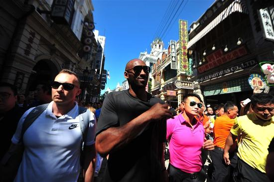 Retired National Basketball Association player and 18-time All-Star Kobe Bryant is surrounded and followed by a crowd of fans as he tours Haikou City, south China's Hainan Province, on September 12, 2017.