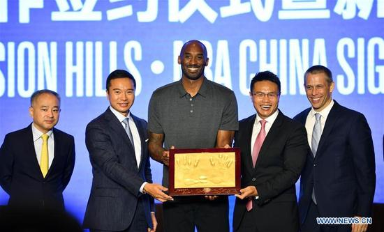 Former NBA basketball player Kobe Bryant (C) poses during a signing ceremony in Haikou, capital of south China's Hainan Province, Sept. 12, 2017. China's Mission Hills Group and NBA China announced on Tuesday a longterm partnership to design, develop and operate an NBA Basketball School as well as an NBA interactive experience and store in Haikou. (Xinhua/Guo Cheng)