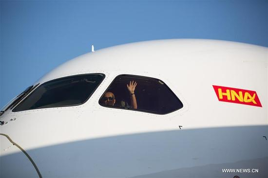 A pilot of Hainan Airlines HU407 flight waves his hand as the flight arrives at Ben Gurion International Airport, near Tel Aviv, Israel, on Sept. 12, 2017. China's Hainan Airlines operated its new direct flight HU407 between Shanghai and Tel Aviv starting Tuesday. The three-times-a-week flight will operate using a Boeing 787-9. (Xinhua/Guo Yu)
