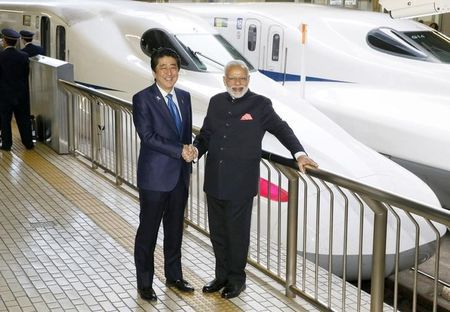 Indian Prime Minister Narendra Modi (R) and Japan's Prime Minister Shinzo Abe pose in front of a Shinkansen bullet train before heading for Hyogo prefecture at Tokyo Station, Japan November 12, 2016, in this photo