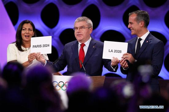 International Olympic Committee President Thomas Bach (C) poses for photos with Anne Hidalgo (L), Mayor of Paris, and Eric Garcetti, Mayor of Los Angeles, at the 131st IOC session in Lima, Peru, on Sept. 13, 2017. The International Olympic Committee (IOC) has confirmed Paris and Los Angeles as the Summer Olympics host cities for 2024 and 2028 respectively, through a vote by a show of hands on Wednesday in Lima, Peru. (Xinhua/Luis Camacho)