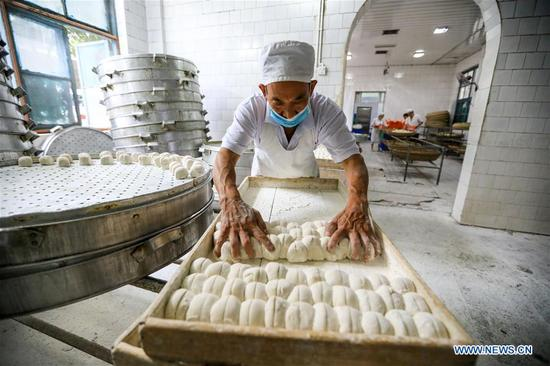 A worker makes Baoning sweet steamed buns at a bakery in Langzhong, southwest China's Sichuan Province, Sept. 12, 2017. As a local intangible cultural heritage, the special steamed bun here gained great reputation in the area. For hundreds of years, the bun has been produced under 21 complete procedures, and finished with a red stamp proving the authenticity. (Xinhua/Liu Chan)
