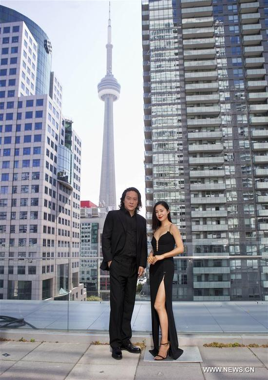 """Director Zhao Hantang (L) and actress Jiang Yiyan pose for photos with the Canadian National Tower (CN Tower) before the press conference of the North American premiere of Chinese film """"Seventy-Seven Days"""" in Toronto, Canada, Sept. 13, 2017. (Xinhua/Zou Zheng)"""