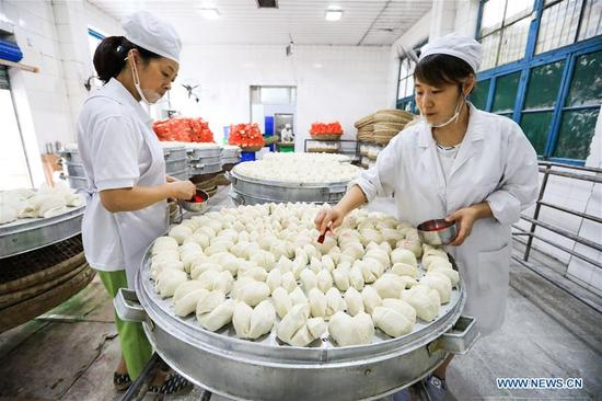 Workers tap red stamps onto finished Baoning sweet steamed buns at a bakery in Langzhong, southwest China's Sichuan Province, Sept. 13, 2017. As a local intangible cultural heritage, the special steamed bun here gained great reputation in the area. For hundreds of years, the bun has been produced under 21 complete procedures, and finished with a red stamp proving the authenticity. (Xinhua/Liu Chan)
