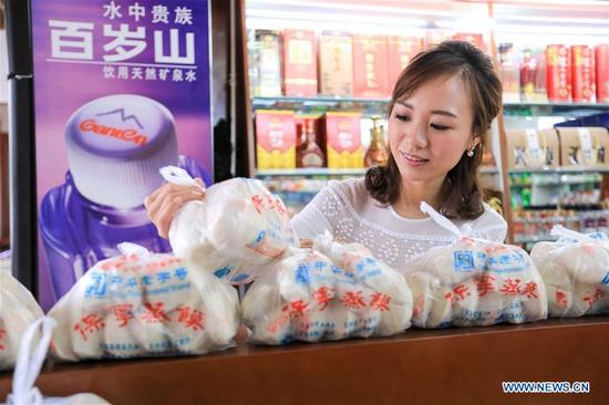 A consumer shops Baoning sweet steamed buns at a grocer in Langzhong, southwest China's Sichuan Province, Sept. 13, 2017. As a local intangible cultural heritage, the special steamed bun here gained great reputation in the area. For hundreds of years, the bun has been produced under 21 complete procedures, and finished with a red stamp proving the authenticity. (Xinhua/Liu Chan)