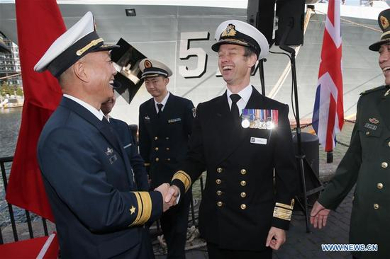 China's 26th naval escort fleet commander Wang Zhongcai (L, front) shakes hands with British Rear Admiral Alex Burton during the welcoming ceremony of China's 26th naval escort fleet in London, Britain, on Oct. 3, 2017. China's 26th naval escort fleet arrived here Tuesday for a five-day friendly visit to Britain. This is the first time for Chinese naval ships to pay an official visit to the British capital city. (Xinhua/Tim Ireland)