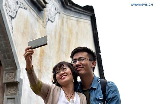Tourists take selfies in Huangling Village of Wuyuan County, east China's Jiangxi Province, Oct. 5, 2017. People find various ways to spend their National Day holidays, from Oct. 1 to Oct. 8 this year. (Xinhua/Hu Dunhuang)