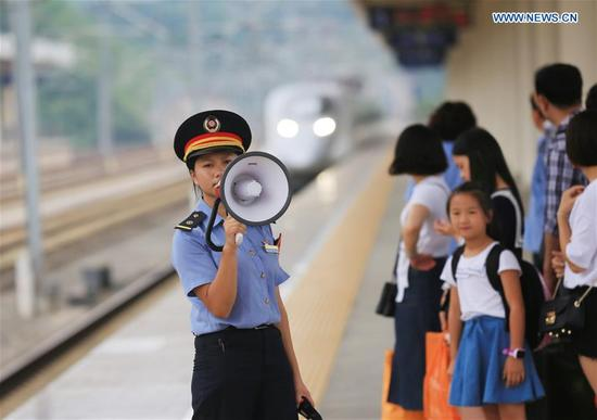 A railway staff member organizes passengers to get on a train at Tongren South Railway Station in southwest China's Guizhou Province, Oct. 2, 2017. People find various ways to spend their National Day holidays, from Oct. 1 to Oct. 8 this year. (Xinhua/Wu Jibin)