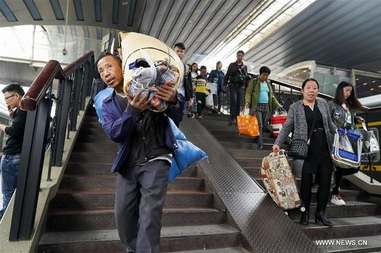 Passengers are seen at Beijing Railway Station in Beijing, capital of China, Oct. 7, 2017. As the National Day holiday draws to its end, Beijing greets a large number of passengers back to work and college. (Xinhua/Shen Bohan)