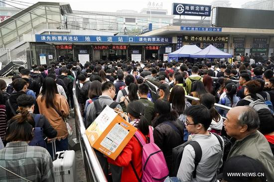 Passengers queue to take a subway after arriving at Beijing Railway Station in Beijing, capital of China, Oct. 7, 2017. As the National Day holiday draws to its end, Beijing greets a large number of passengers back to work and college. (Xinhua/Shen Bohan)