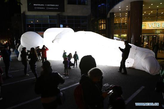 """Visitors watch a light object called """"Fantastic Planet-Humanoid"""" during the contemporary art festival """"White Night 2017"""" in Bratislava, capital of Slovakia, on Oct. 7, 2017. (Xinhua/Andrej Klizan)"""