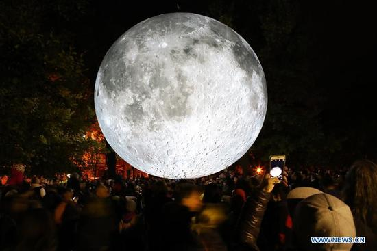 """Visitors watch a light object called """"Museum of the Moon"""" during the contemporary art festival """"White Night 2017"""" in Bratislava, capital of Slovakia, on Oct. 7, 2017. (Xinhua/Andrej Klizan)"""
