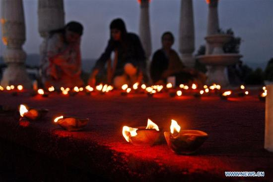 People light oil lamps to mark the 12th anniversary of the devastating 2005 earthquake, in Islamabad, capital of Pakistan, on Oct. 8, 2017. Pakistan was hit by a 7.6-magnitude earthquake on Oct. 8, 2005, which left more than 73,000 people dead and about 3.5 million others homeless. (Xinhua/Saadia Seher)