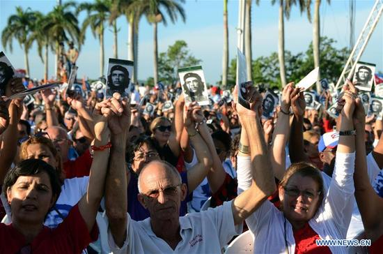 People react during an event commemorating the 50th anniversary of the death of Latin American revolutionary Ernesto