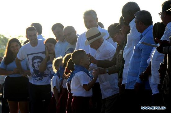 Cuban President Raul Castro interacts with kids during an event commemorating the 50th anniversary of the death of Latin American revolutionary Ernesto