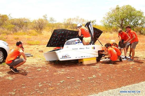 Members of the team for solar vehicle Nuna9 from the Netherlands move the vehicle to the roadside after a flat tyre accident during the second day match of 2017 World Solar Challenge in Canberra, Australia on Oct. 9, 2017. (Xinhua/2017 Bridgestone World Solar Challenge)