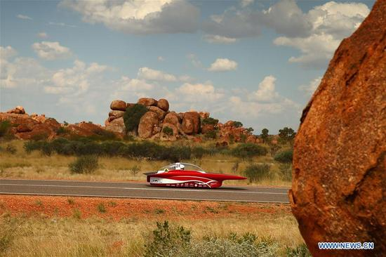 Solar car Red Shift by the Univesity of Twente of the Netherlands races pass Devil's Marble during the second day match of 2017 World Solar Challenge in Canberra, Australia on Oct. 9, 2017. (Xinhua/2017 Bridgestone World Solar Challenge)