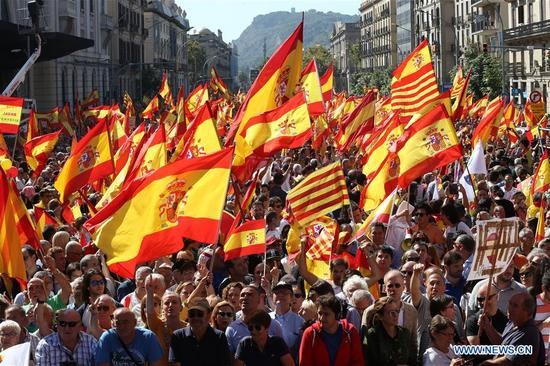 "People wave Spanish national flags in a march with the slogan ""Enough and let's recover the sensibility"", to defend the Spanish constitution and the unity of Spain in Barcelona, Spain, Oct. 8, 2017. (Xinhua/Juan Carlos Rojas)"