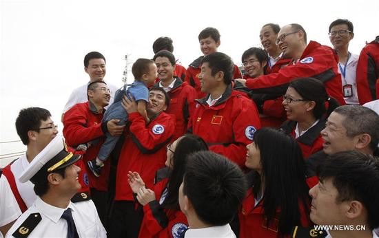 Shi Xing'an (2nd R, rear), a member of the Chinese scientific expedition team, is welcomed by his son upon his return in Shanghai, east China, Oct. 10, 2017. China's ice breaker, the Xuelong (Snow Dragon) returned to base in Shanghai Tuesday after 83 days on the Arctic rim, completing its eighth Arctic expedition. (Xinhua/Fang Zhe)