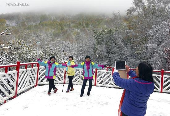 Tourists take pictures in Labagou Forest Scenic Resort in Huairou District of Beijing, capital of China, Oct. 10, 2017. The resort greeted snow on Tuesday. (Xinhua/Bu Xiangdong)