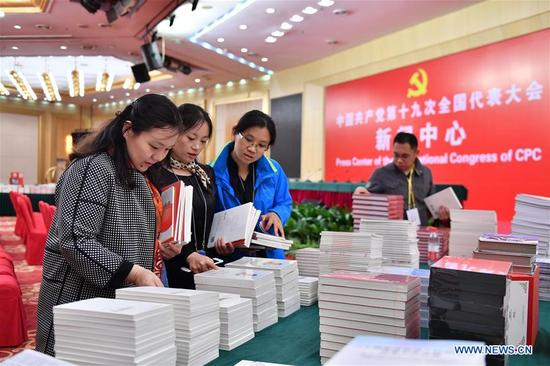 Journalists take books and materials in the press conference hall of the Press Center of the 19th National Congress of the Communist Party of China in Beijing, capital of China, Oct. 11, 2017. The press center based in the Beijing Media Center Hotel began operations on Wednesday. (Xinhua/Li Xin)