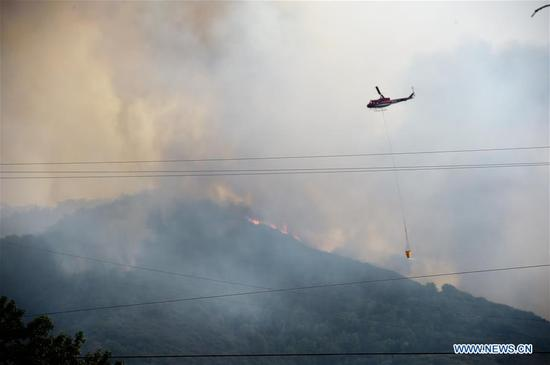 A helicopter tries to put out the wildfire in California's Napa, the United States, on Oct. 10, 2017. (Xinhua/Wu Xiaoling)