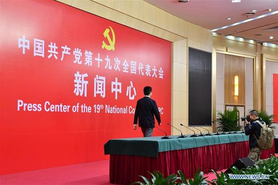 A cameraman (R) takes photos in the press conference hall of the Press Center of the 19th National Congress of the Communist Party of China in Beijing, capital of China, Oct. 11, 2017. The press center based in the Beijing Media Center Hotel began operations on Wednesday. (Xinhua/Li Xin)