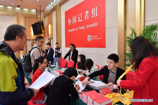Staff members work at the reception for foreign journalists in the Press Center of the 19th National Congress of the Communist Party of China in Beijing, capital of China, Oct. 11, 2017. The press center based in the Beijing Media Center Hotel began operations on Wednesday. (Xinhua/Li Xin)