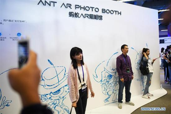 "Visitors try an AR photo booth on ""The Computing Conference 2017"" in Hangzhou, capital of east China's Zhejiang Province, Oct. 11, 2017. The four-day conference kicked off here on Wednesday, attracting guests from 67 countries and regions. (Xinhua/Huang Zongzhi)"