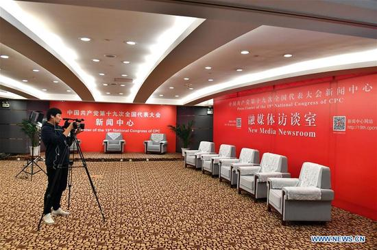 A journalist takes video in the new media newsroom of the Press Center of the 19th National Congress of the Communist Party of China in Beijing, capital of China, Oct. 11, 2017. The press center based in the Beijing Media Center Hotel began operations on Wednesday. (Xinhua/Li Xin)