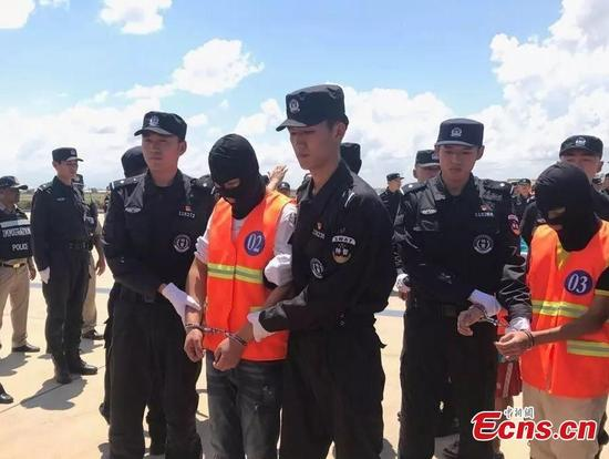 Chinese nationals suspected of involvement in transnational telecom fraud, and set to be deported from Cambodia, arrive at Phnom Penh International Airport to fly back to China on a chartered plane, Oct. 12, 2017, under the escort of Chinese police. The 74 suspects, including 14 women, were involved in more than 60 cases of major transnational telecom fraud involving more than 7 million yuan ( .1 million). (Photo: China News Service/Zhong Xin)