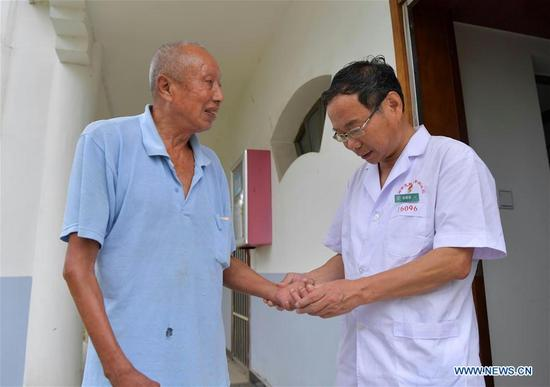 Dermatologist Xu Genbao (R) gives medical check for a patient at the rehabilitation center of Jiangxi Province Dermatosis Special Hospital in suburban Nanchang City, capital of east China's Jiangxi Province, Sept. 29, 2017. Xu has worked in this isolated center for leprosy disease for 28 years. He has been elected as a delegate to attend the 19th National Congress of the Communist Party of China (CPC) in Beijing from Oct. 18.