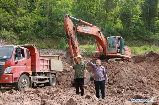 Jiang Yijia (R), secretary of the Communist Party of China (CPC) committee of Gongshi Village, gives directions at the construction site of a service center for villagers in Gongshi Village of Pengxi County, southwest China's Sichuan Province, May 4, 2017. Jiang, a veteran and enterpreneur, returned to his hometown as a CPC cadre at the age of 49 to help the villagers get rid of poverty. Now Jiang has been elected as a delegate to attend the Party's 19th National Congress in Beijing from Oct. 18.
