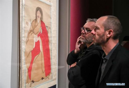 """Two visitors look on a painting during the Chinese portrait painting exhibition """"Faces of China, Portrait Painting of the Ming and Qing Dynasties (1368-1912)"""" in Berlin, capital of Germany, on Oct. 11, 2017. Europe's first-ever grand exhibition explicitly dedicated to Chinese portrait paintings was unveiled in Berlin in the evening of Wednesday, the day China and Germany celebrated the 45th anniversary of the establishment of diplomatic ties. (Xinhua/Shan Yuqi)"""