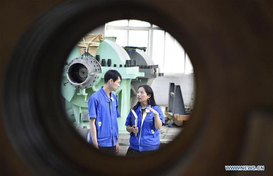 Deputy Chief Engineer Jiang Yan (R) talks with her colleague at a workshop in a design institute of Shenyang Blower Works Group in Shenyang, capital of northeast China's Liaoning Province, Sept. 21, 2017. Jiang has devoted her efforts to the domestically developed technology of ethylene compressor. She has been elected as a delegate to attend the 19th National Congress of the Communist Party of China (CPC) in Beijing from Oct. 18.