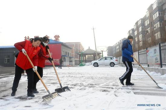 Wu Yaqin (1st L), a community worker, cleans snow in Changshan Garden community of Changchun City, capital of northeast China's Jilin Province, March 6, 2017. Wu has served as a community worker for over 20 years. She has been elected as a delegate to attend the 19th National Congress of the Communist Party of China (CPC) in Beijing from Oct. 18.