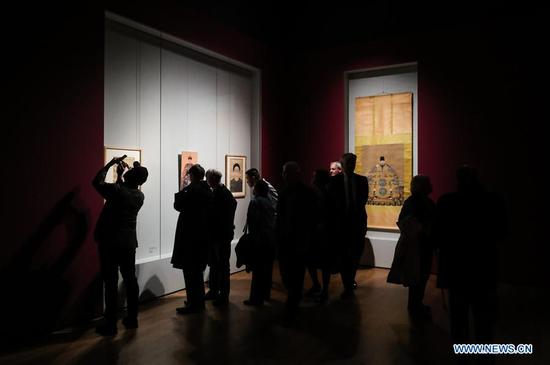 """Visitors look on paintings during the Chinese portrait painting exhibition """"Faces of China, Portrait Painting of the Ming and Qing Dynasties (1368-1912)"""" in Berlin, capital of Germany, on Oct. 11, 2017. Europe's first-ever grand exhibition explicitly dedicated to Chinese portrait paintings was unveiled in Berlin in the evening of Wednesday, the day China and Germany celebrated the 45th anniversary of the establishment of diplomatic ties. (Xinhua/Shan Yuqi)"""