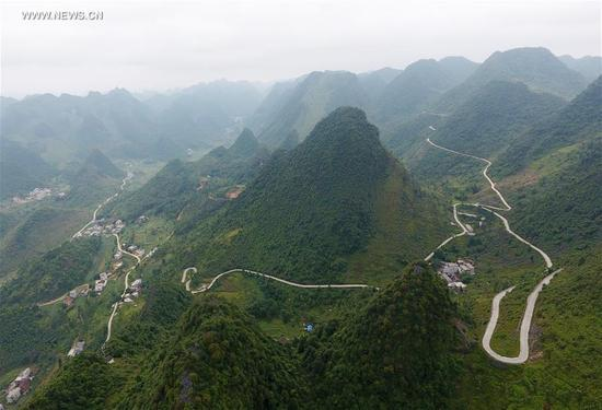 Photo taken on Oct. 12, 2017 shows a country road in Xia'ao Town of Du'an Yao Autonomous County, south China's Guangxi Zhuang Autonomous Region. The county has an area of 4,000 square kilometers of which 89 percent is covered by stony mountains. The counstruction of country roads link local people with the outside world and help them to alleviate poverty. (Xinhua/Lu Boan)