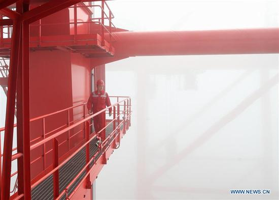 Zhang Yan, a container crane operator, walks to his working place high above the ground at the container terminal of Yangshan Port in Shanghai, east China, Sept. 26, 2017. Zhang, a young man born in 1980s, has been elected as a delegate to attend the 19th National Congress of the Communist Party of China (CPC) in Beijing from Oct. 18.