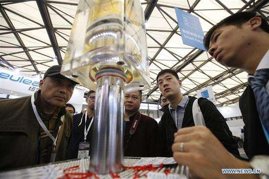 Visitors watch an operation demonstration of hydraulic cylinder model at the 2017 Power Transmission and Control Asia in Shanghai, east China, Oct. 31, 2017. About 2,500 enterprises from home and abroad participated in the event, which focused on intelligent manufacturing this year. (Xinhua/Fang Zhe)